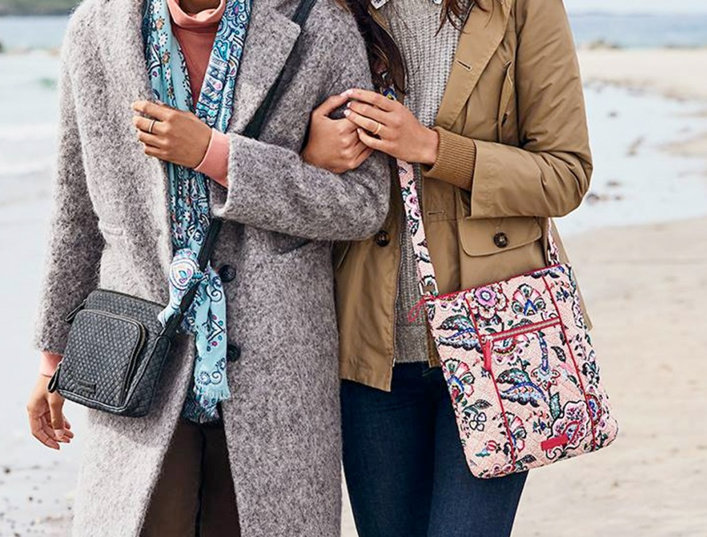 two women walking along beach with crossbody bags in grey and pink paisley print