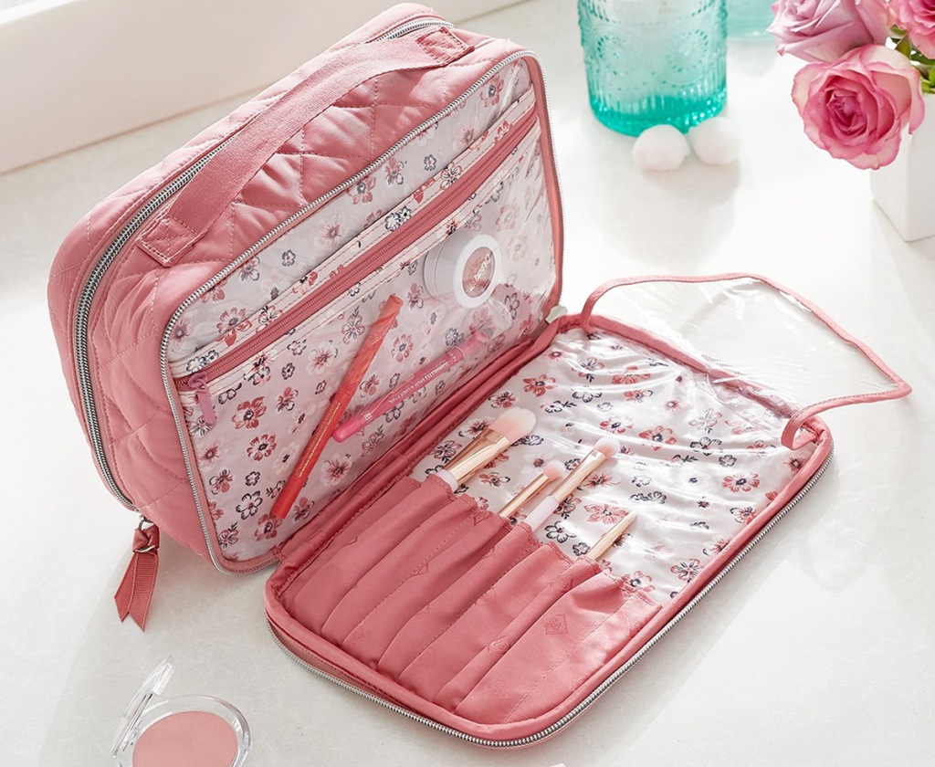 pink makeup case on bathroom counter with clear interior pockets