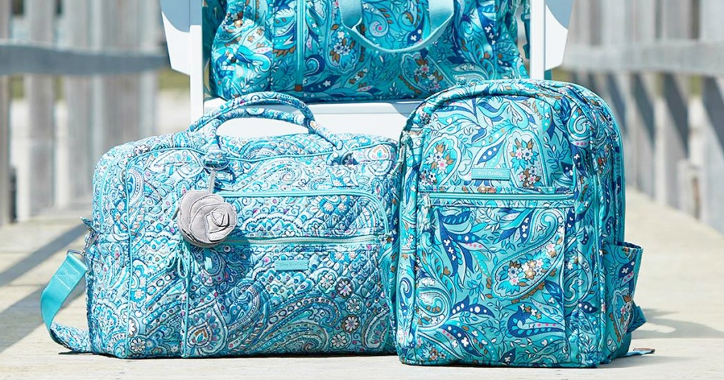 blue paisley print duffle bag and backpack sitting in front of white outdoor chair on a deck