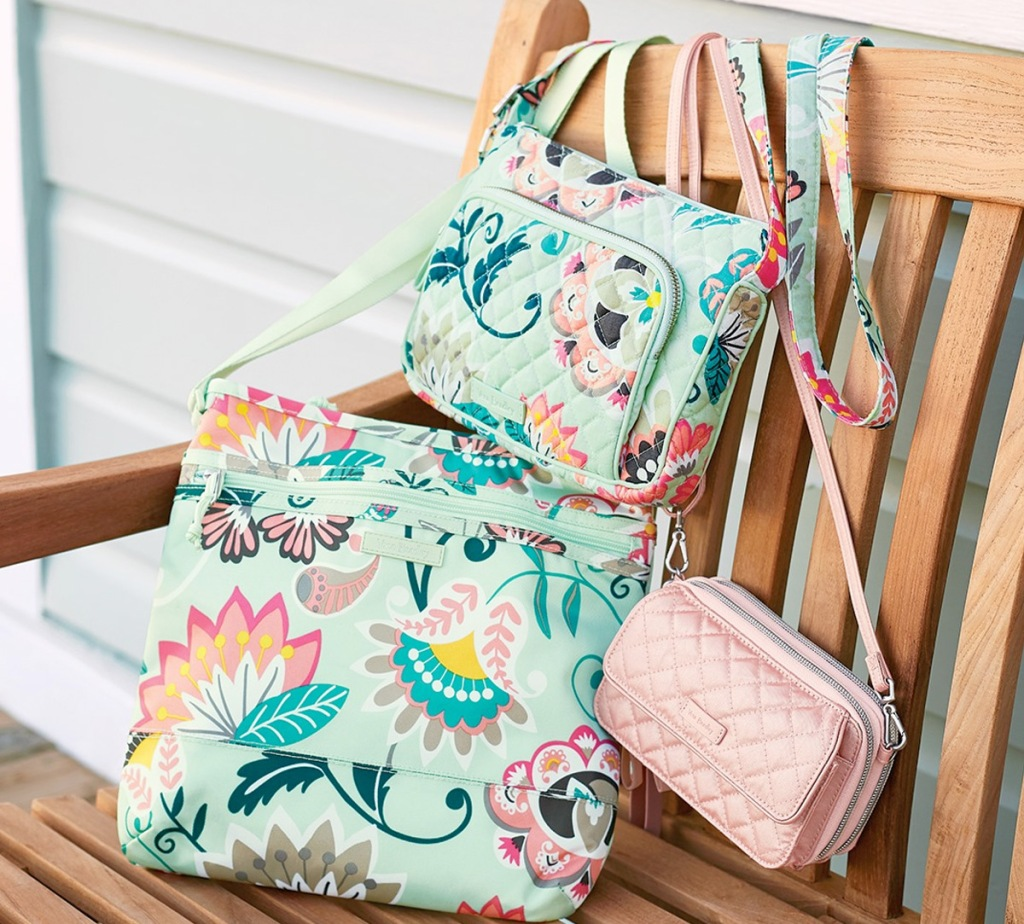 mint colored floral print crossbody bags sitting on a wooden patio chair