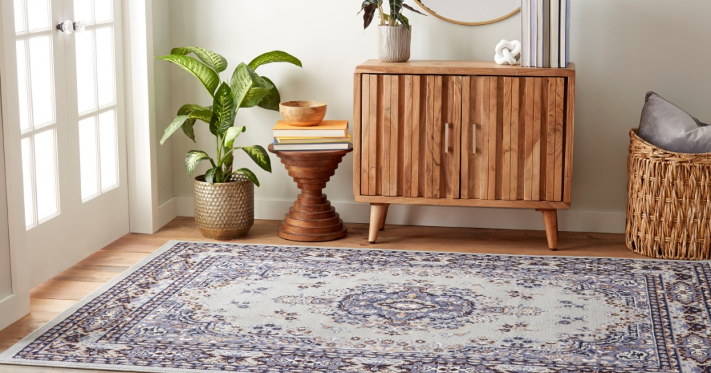 light blue multi-colored area rug on the floor in a home next to a plant, table and cupboard
