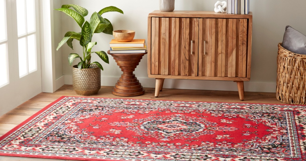 red multi-colored area rug on floor next to a side table and plant
