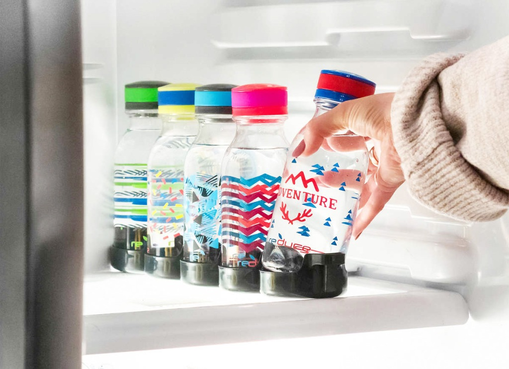 person reaching hand into fridge to grab a red and blue printed water bottle