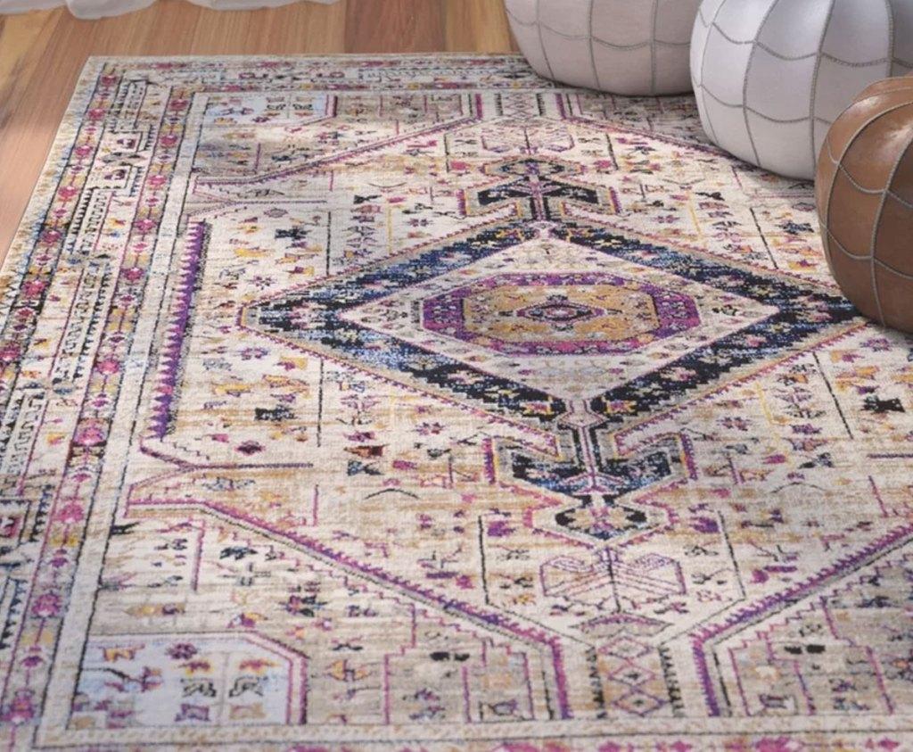 cream, pink, and blue oriental area rug on hardwood floor
