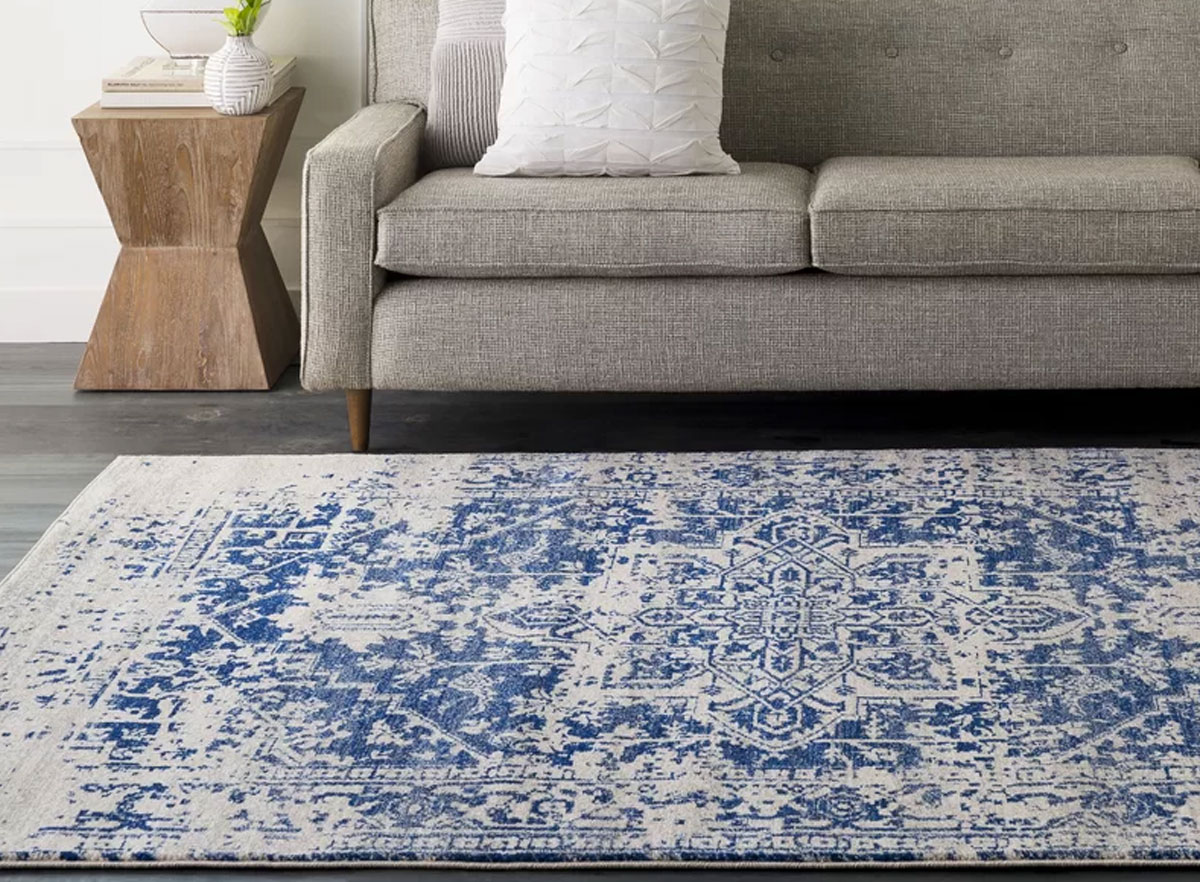 blue and white oriental area rug on floor in front of grey couch