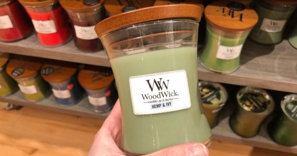 hand holding woodwick candle hemp & ivy