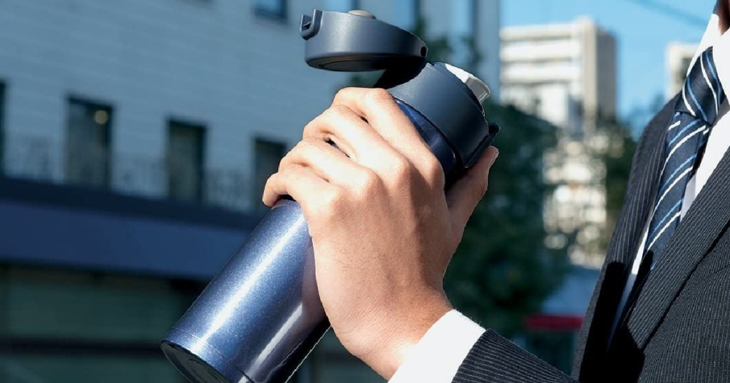 man outside in suit holding open blue stainless steel thermos