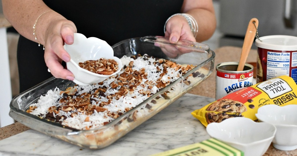 adding chopped pecans to magic cookie bars