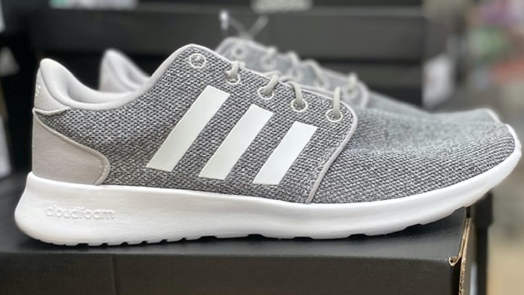women's light grey and white sneakers sitting on shoe box in store
