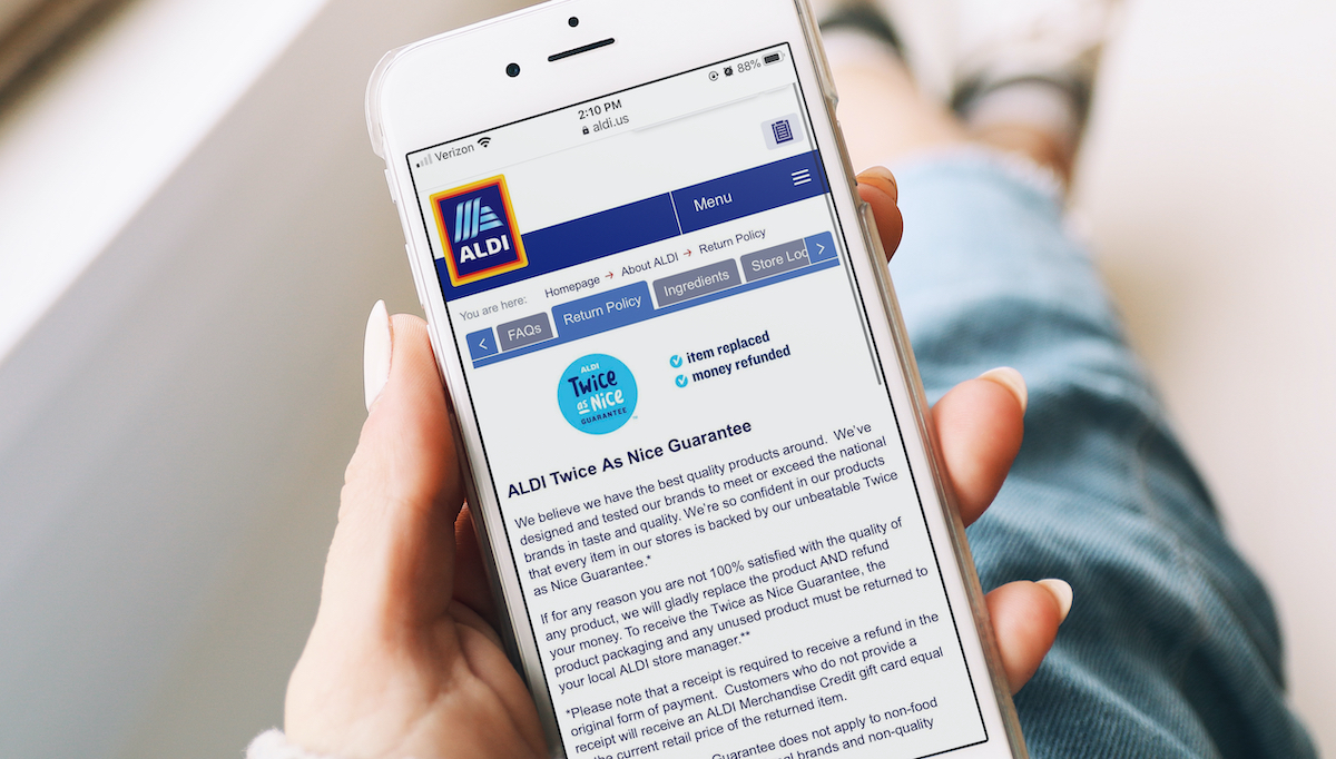 aldi shopping tips hand holding an iphone with aldi return policy on screen