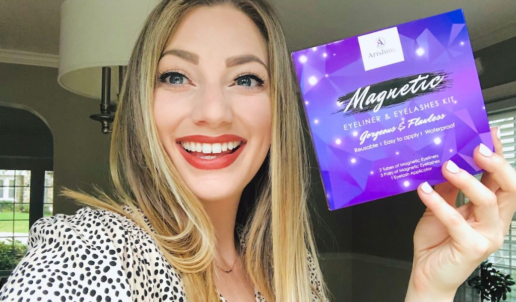 woman smiling wearing magnetic lashes holding purple lash kit box