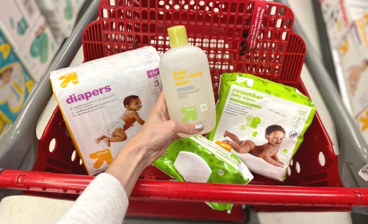 diapers, baby shampoo, and wipes in a shopping cart