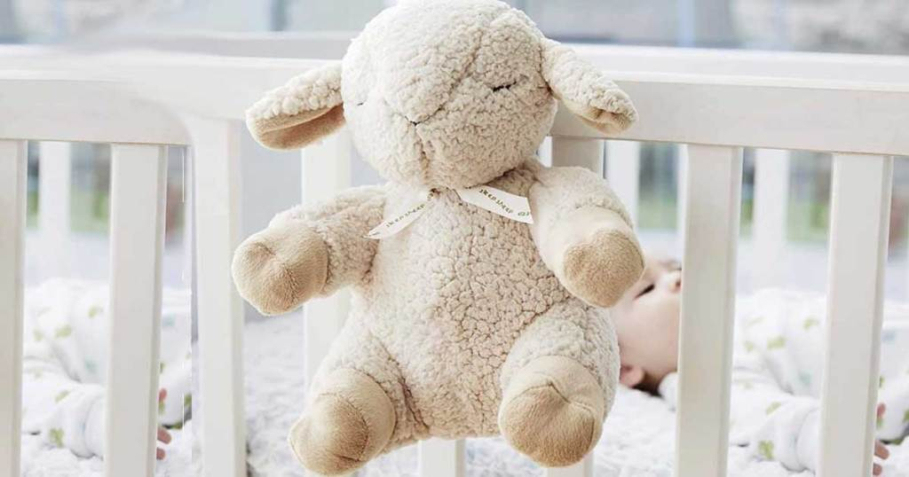 stuffed sheep with sound machine on a crib