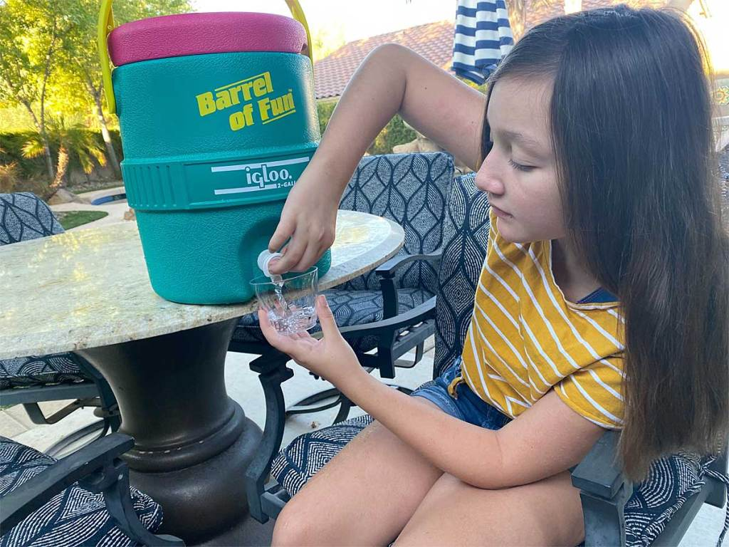 young girl pouring water out of cooler