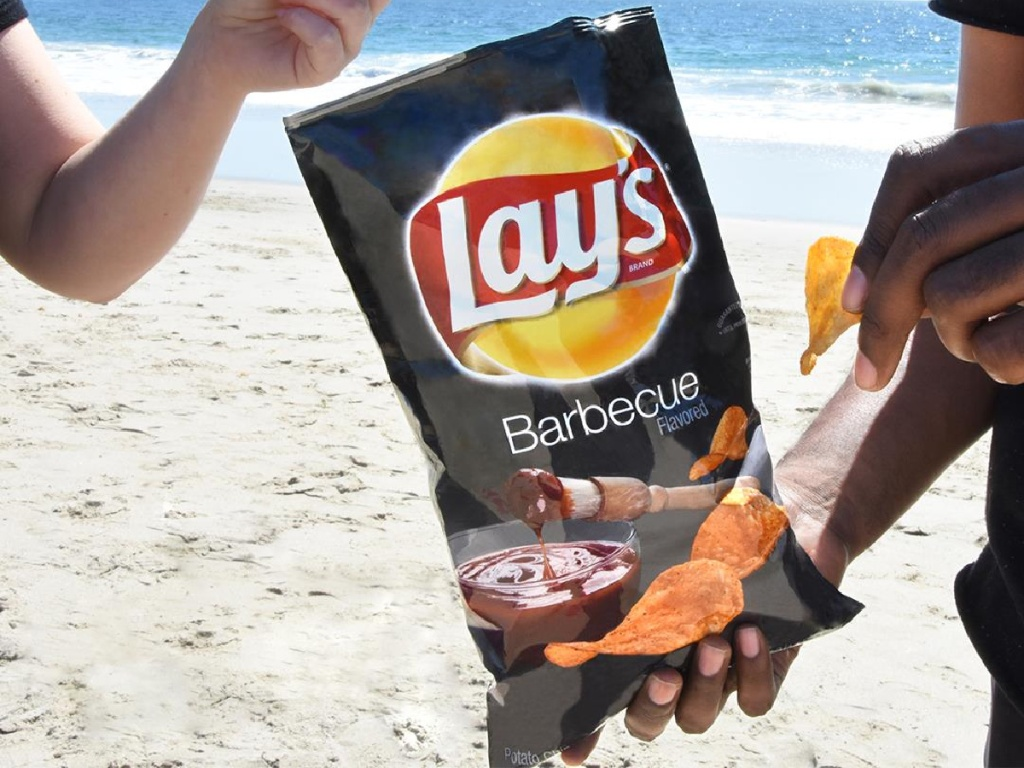 hands taking chips out of Lay's BBQ Chips on the beach