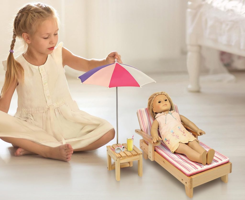 girl playing with her doll who is laying in beach lounger