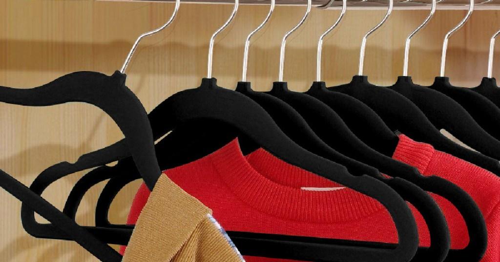 black felt hangers holding sweaters