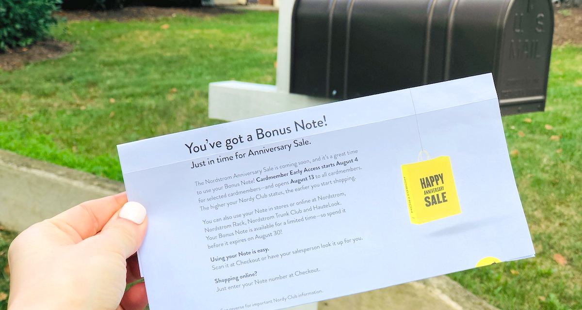 hand holding a piece of nordstrom anniversary sale mail in front of mailbox