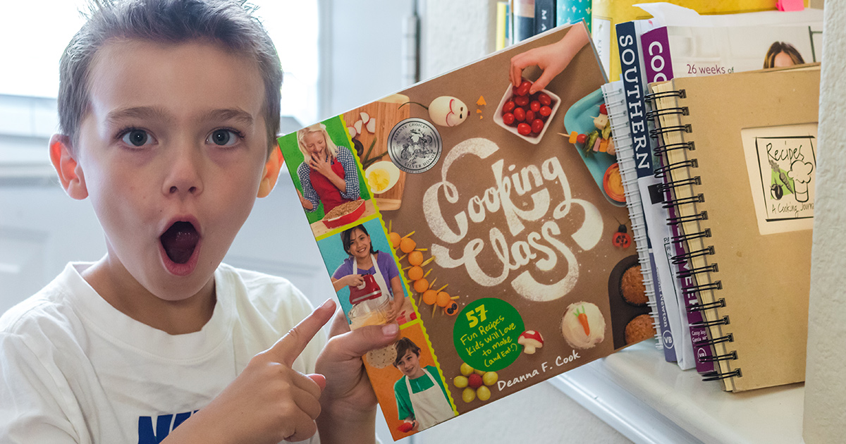 young boy holding cooking class cookbook for kids
