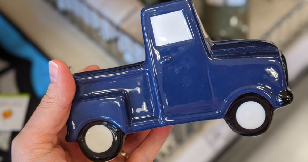 hand holding blue ceramic truck by store display