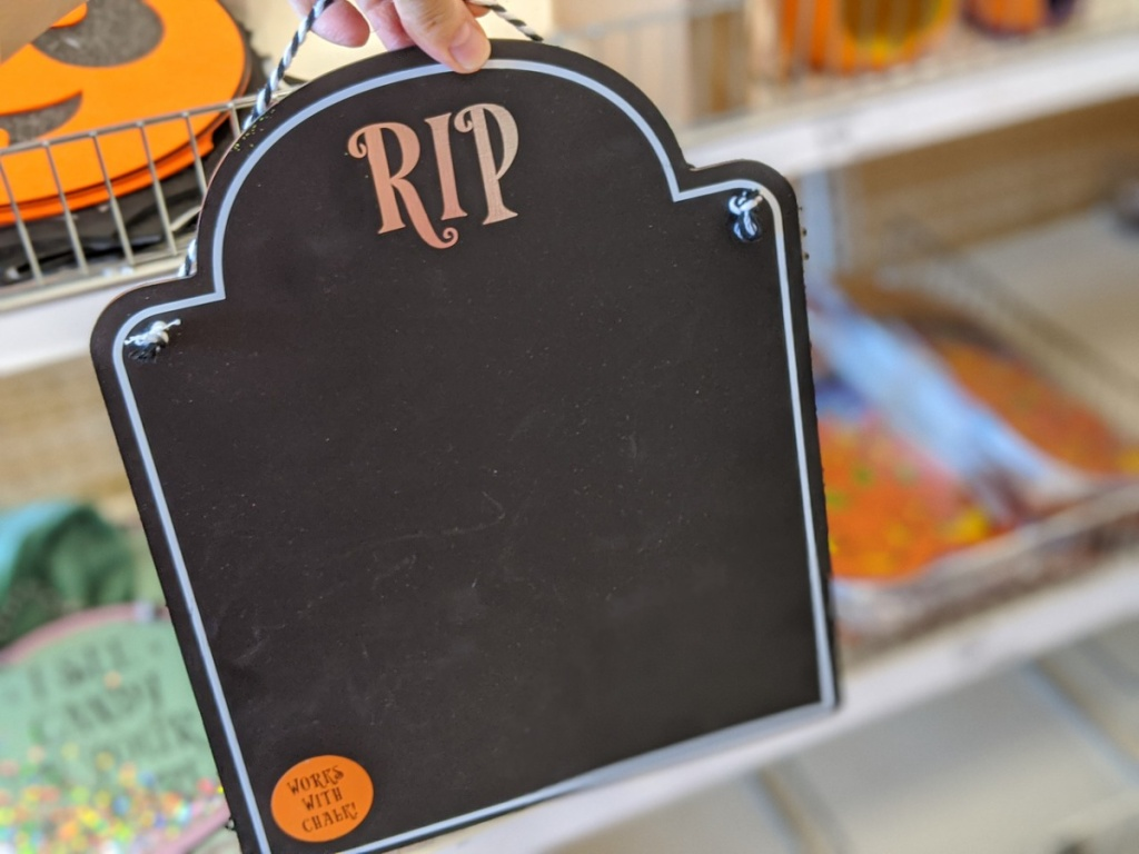 hand holding up chalkboard sign in store