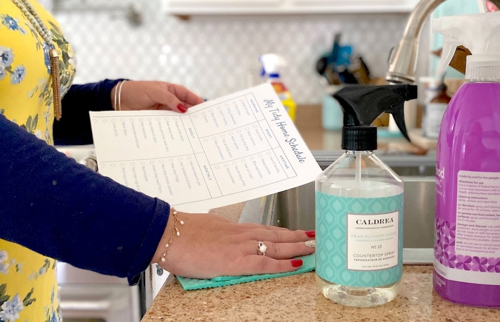 woman holding printable chore chart while wiping countertop