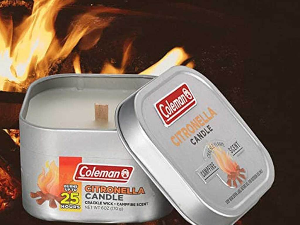 coleman camping candles with a fire behind it