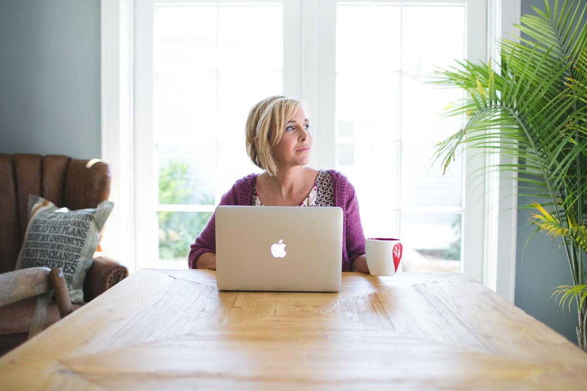 woman sitting with coffee mug and Macbook