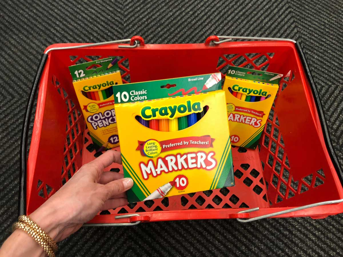 holding box of crayola markers near red basket