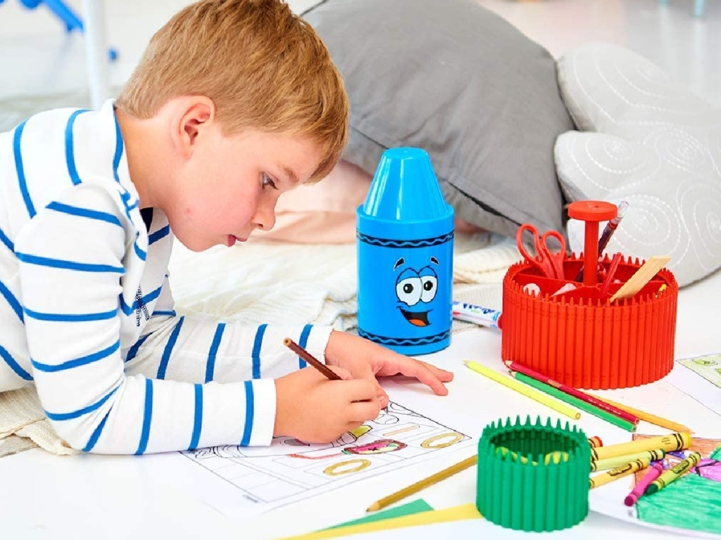 boy coloring on floor with crayons
