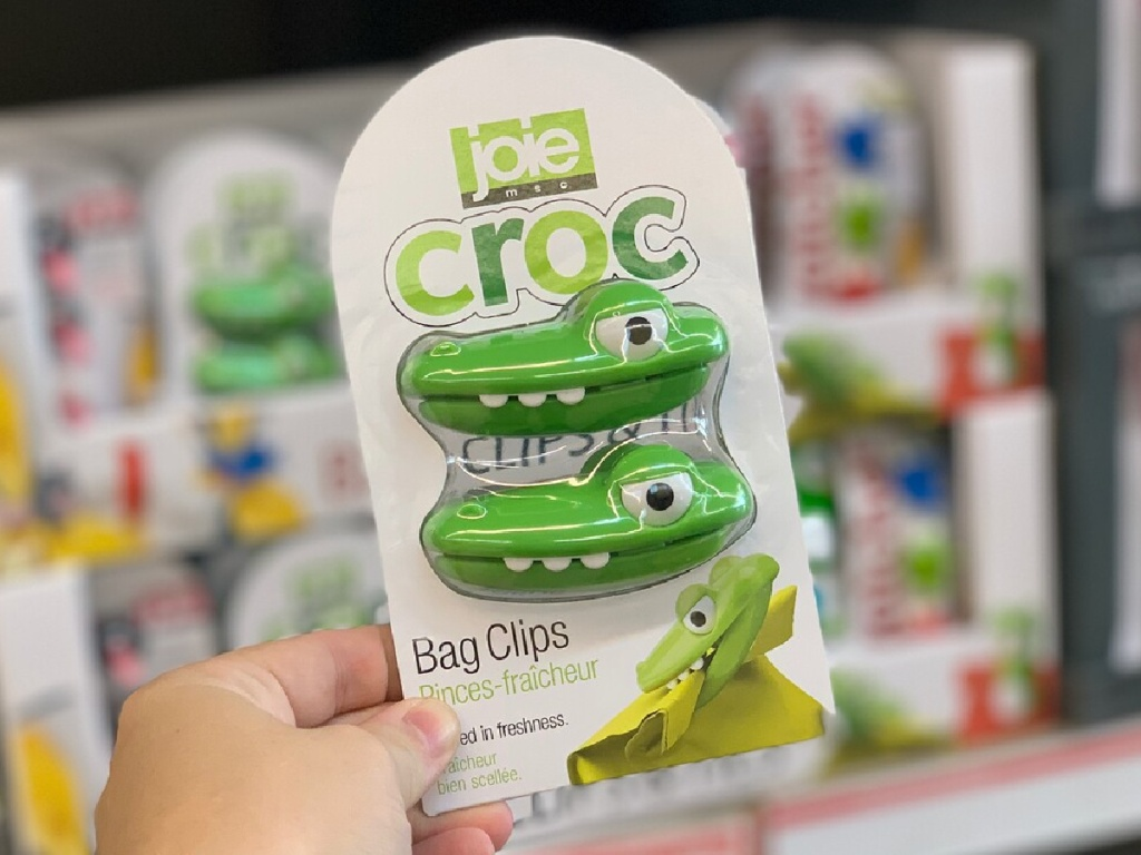 hand holding crocodile shaped bag clips in front of store display