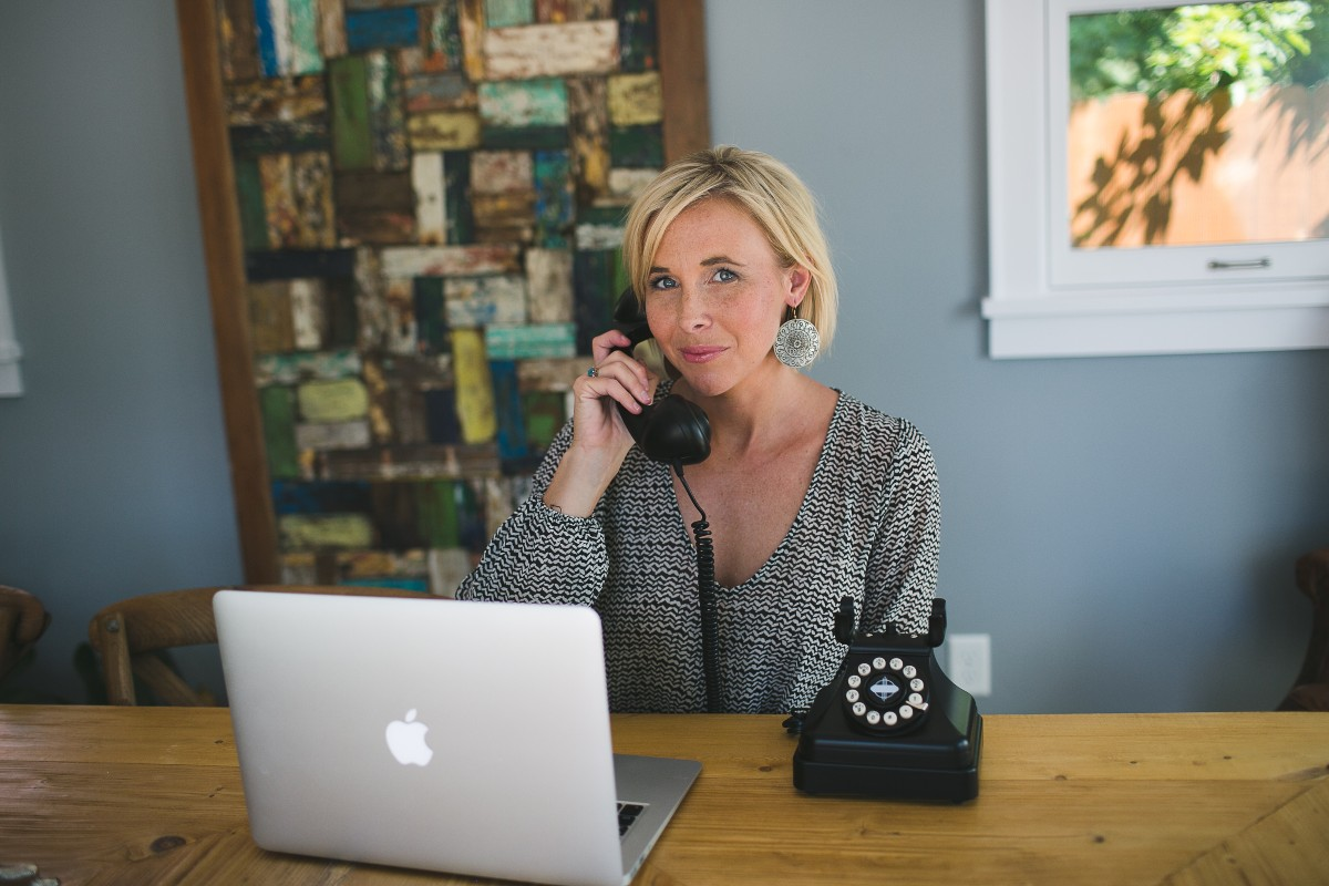 woman talking on phone in front of Macbook