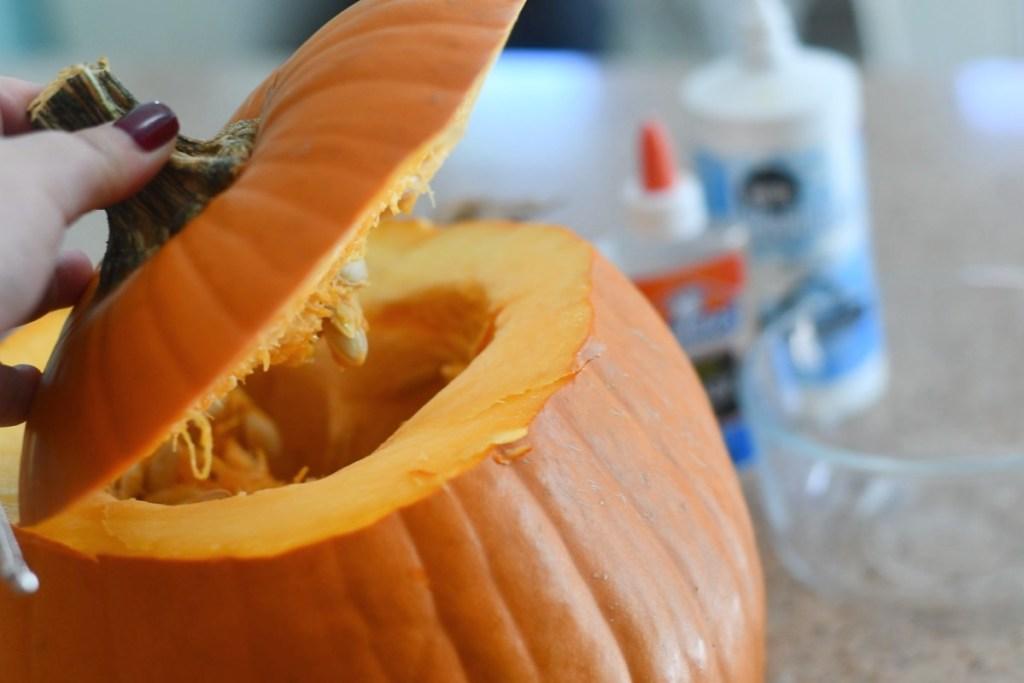 lifting top of cut pumpkin