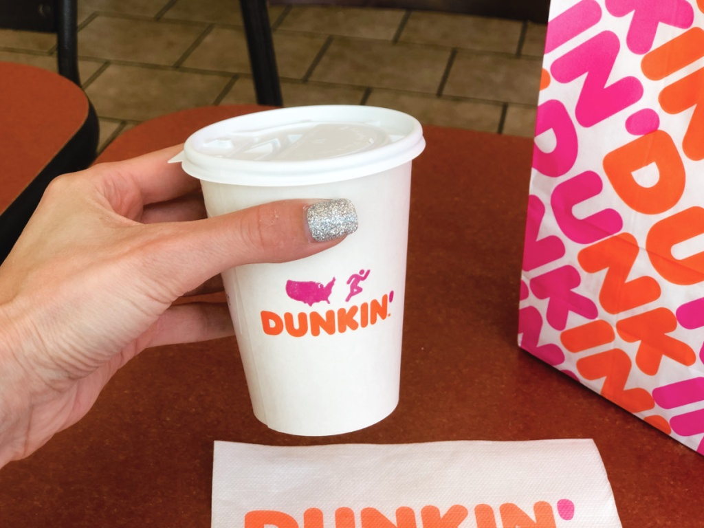 holding a cup of coffee from Dunkin'