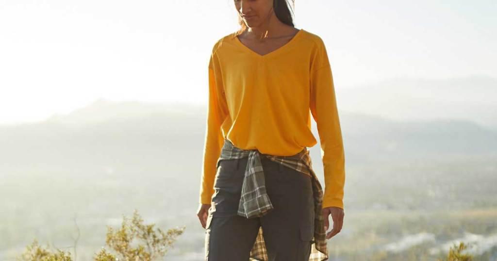 women on a mountain wearing a yellow long sleeve shirt