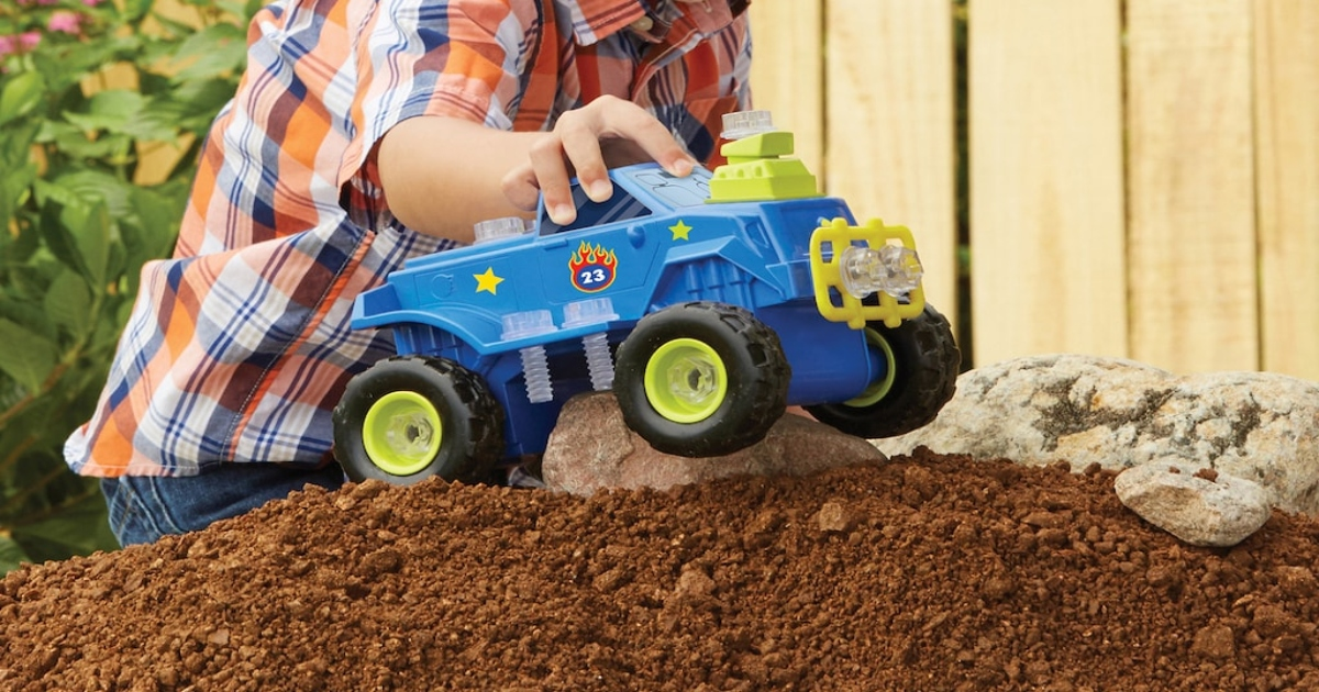 boy playing with blue monster truck on a pile of dirt