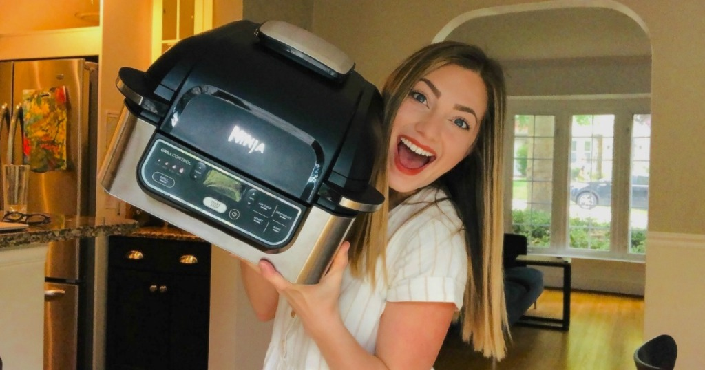 woman holding kitchen appliance with smile on her face