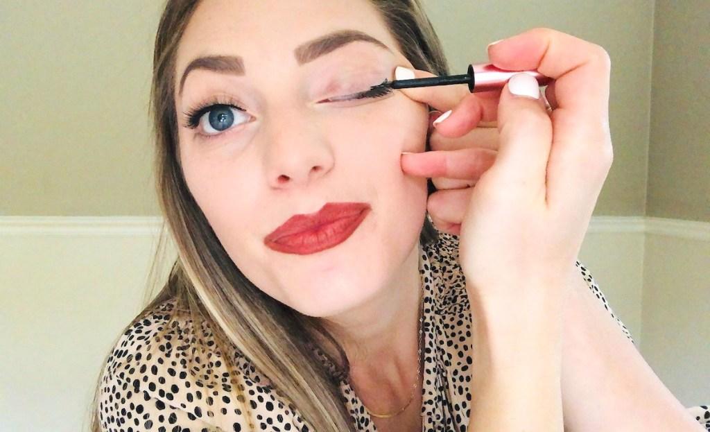 woman putting on black liquid eyeliner
