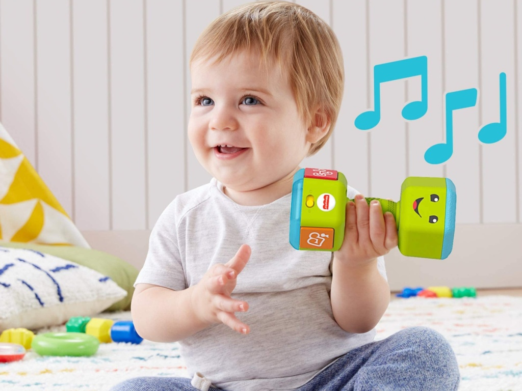 baby sitting on the flooring holding a musical green dumbbell