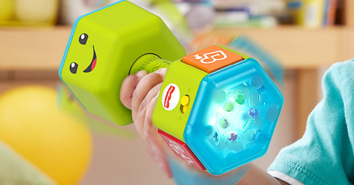 baby holding green toy dumbbell