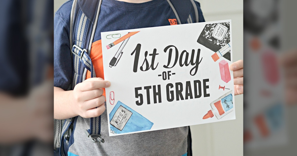 boy holding 1st day of school sign