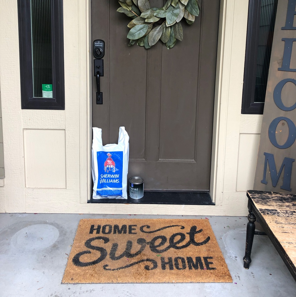 brown front door with a bag from sherwin williams