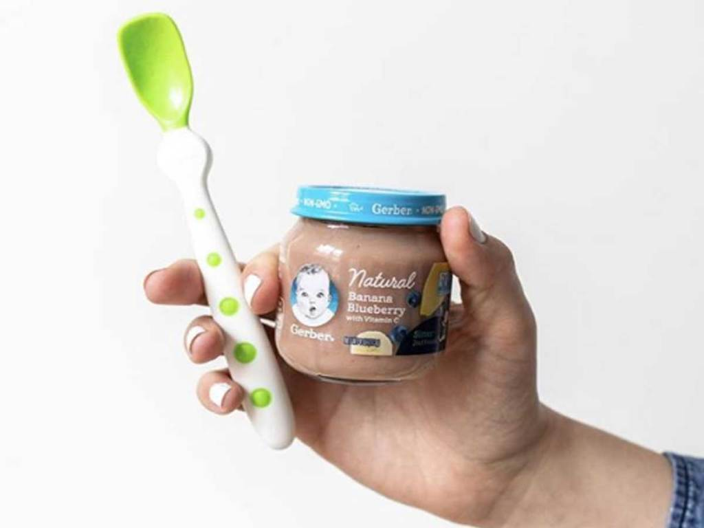 hand holding baby food jar and spoon