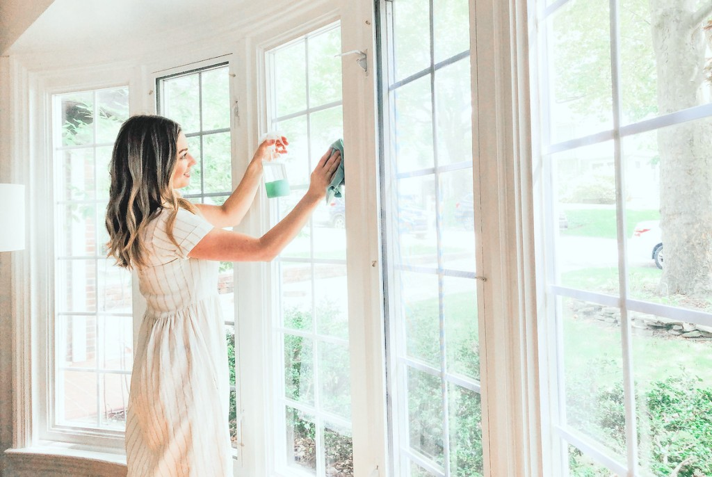 woman cleaning window inside