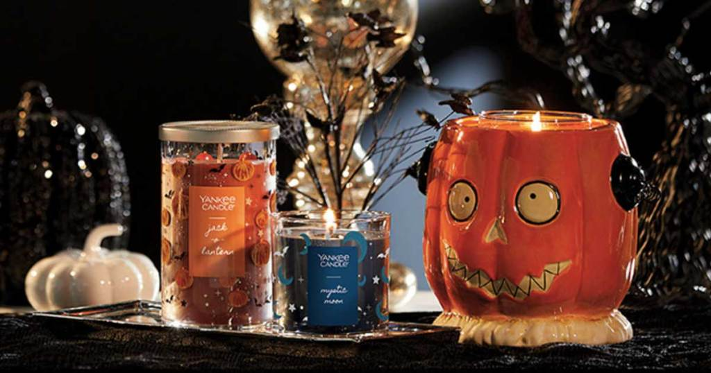 orange and blue halloween candles and a pumpkin candle holder