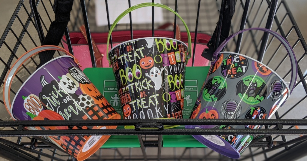 shopping basket with three small buckets with Halloween decorations on them