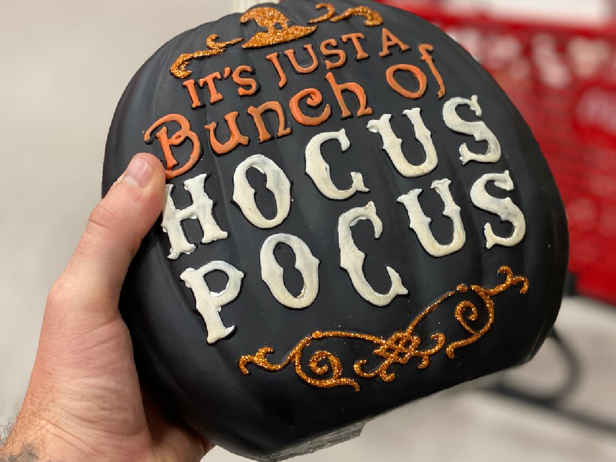 hand holding pumpking with spooky words on it