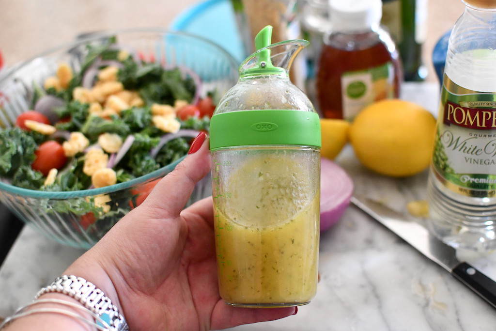 holding salad dressing shaker with salad in the background