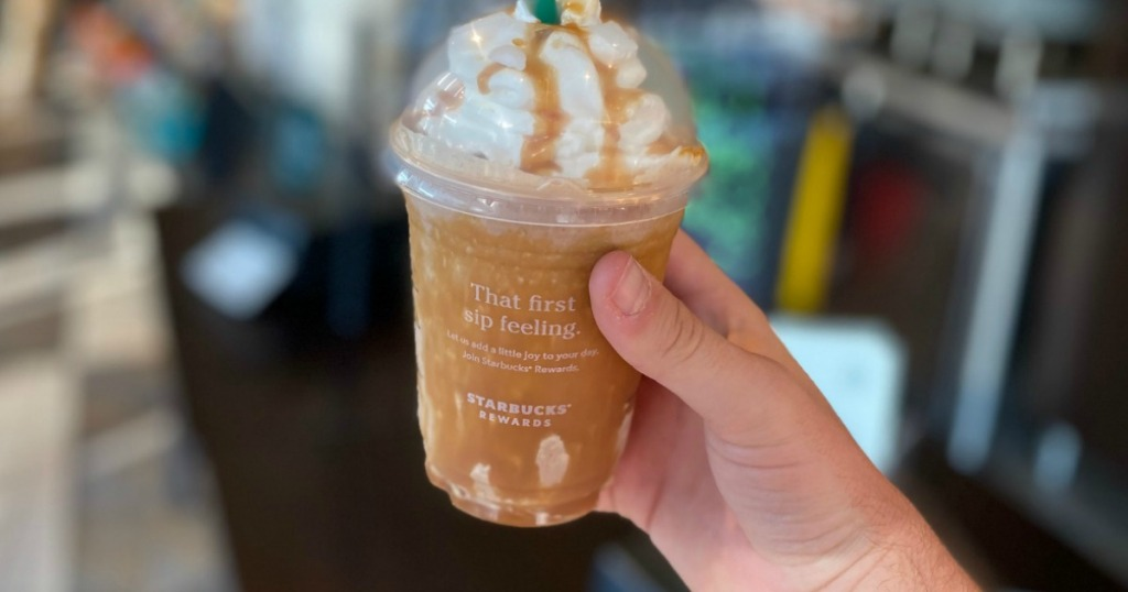 man holding Starbucks frappuccino with whipped cream