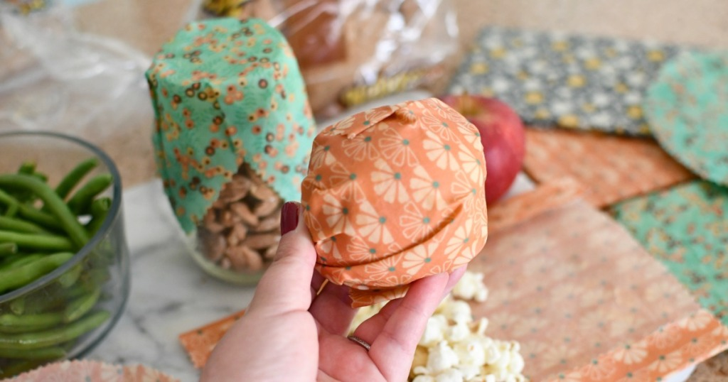 holding up an apple with beeswax wrap